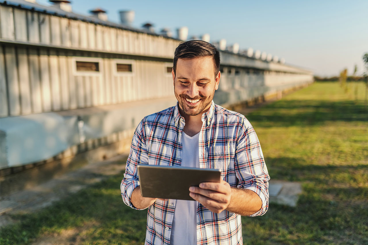 Cheerful farmer standing outdoors using broadband internet service on tablet device