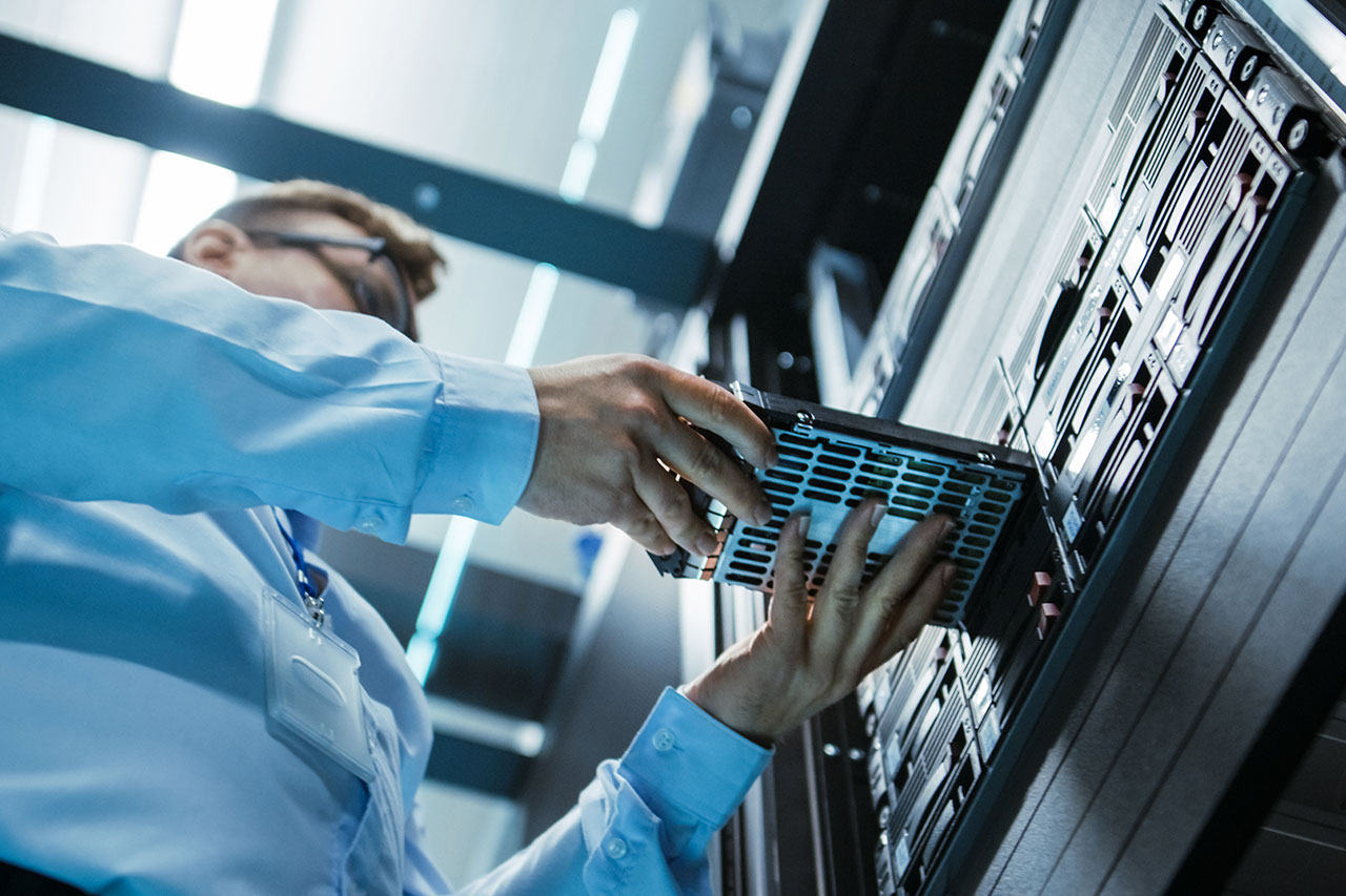Data center IT engineer installing a cyber secure hard drive into server rack