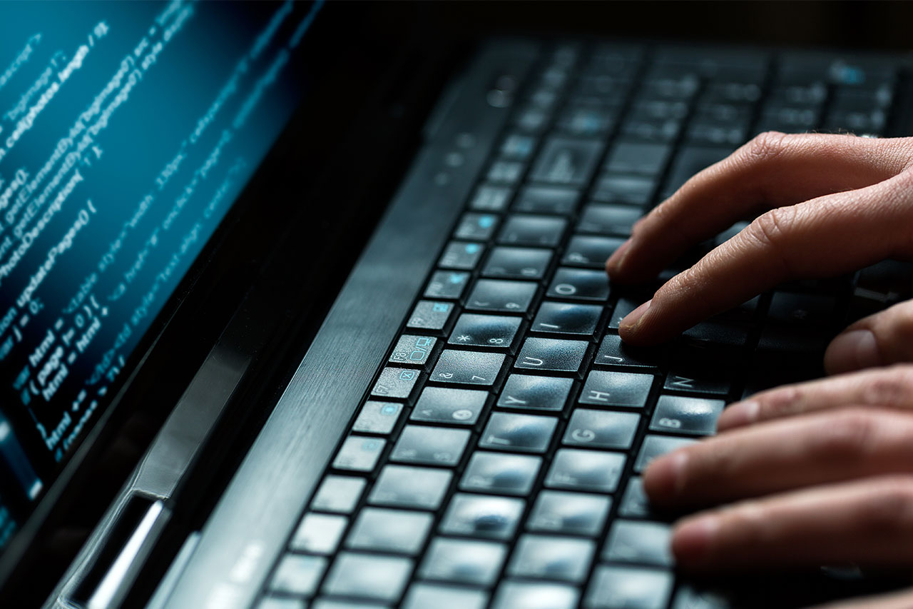 Close up of cybersecurity programmer's hands coding on laptop